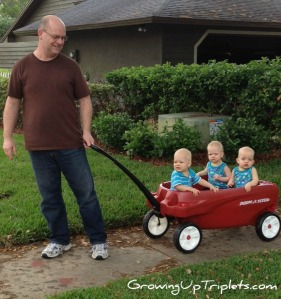 Papa walking the grand-triplets.